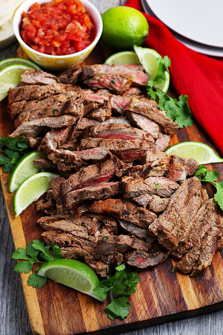 Sliced carne asada meat with limes and cilantro on a wooden cutting board and a bowl of salsa.