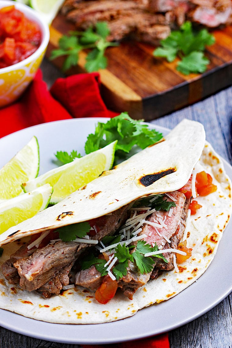 Closeup of a carne asada taco on a white plate with limes with a bowl of salsa and carne asada meat on a cutting board in the background.