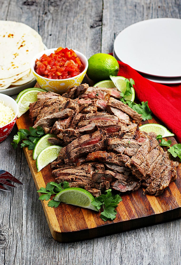 Sliced carne asada meat on a cutting board with a bowl of salsa and slices of lime, white plates, a red napkin, and a pile of flour tortillas.