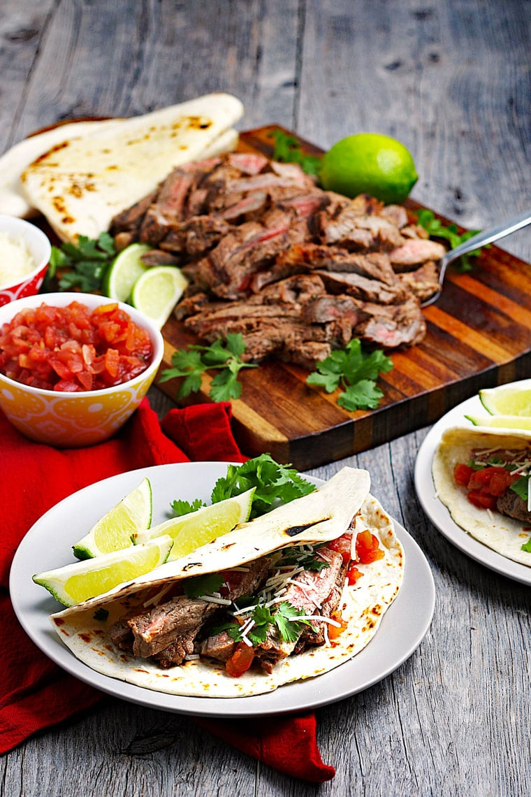 Plates of carne asada tacos with sliced meat on a wooden cutting board with a bowl of salsa and tortillas in the background.