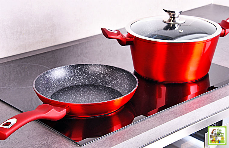 Frying pan and steel pot on modern induction cooktop stove.