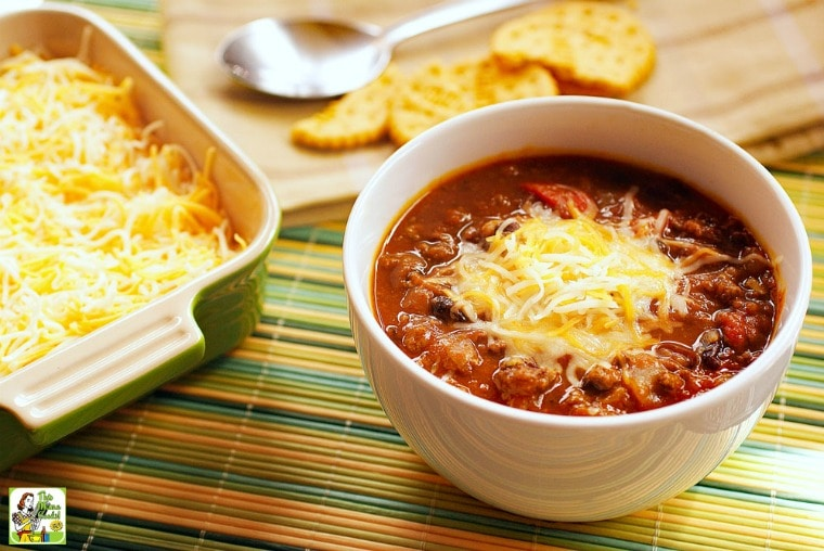A bowl of Slow Cooker Pumpkin Chili with a container of shredded cheese, a wooden cutting board, crackers, and a wooden cutting board all on a bamboo mat.