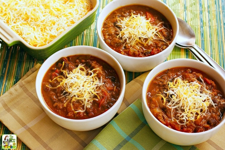 Three white bowls of turkey pumpkin chili with beans covered with shredded cheese