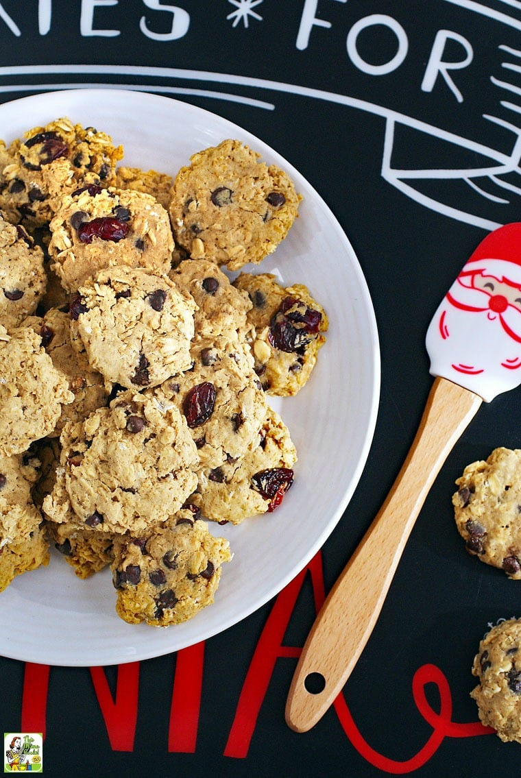 Cookies for Santa placemat with a plate of gluten free oatmeal cookies with chocolate chips and raisins and a Santa spatula.