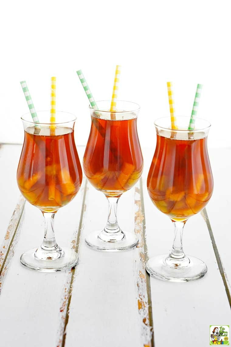 Three tall glasses of Fruit Iced Tea with yellow and green straws.