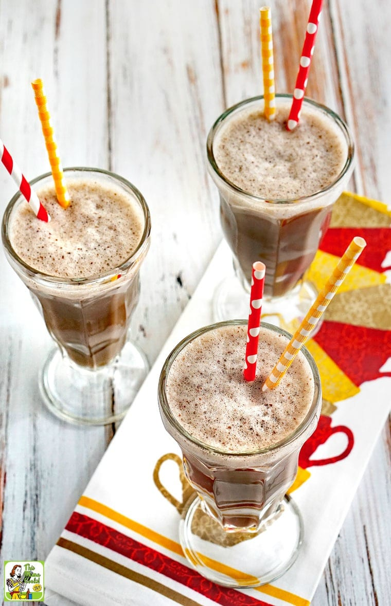 Three tall glasses of Coffee Breakfast Smoothie with yellow and red straws on a colorful tea towel.