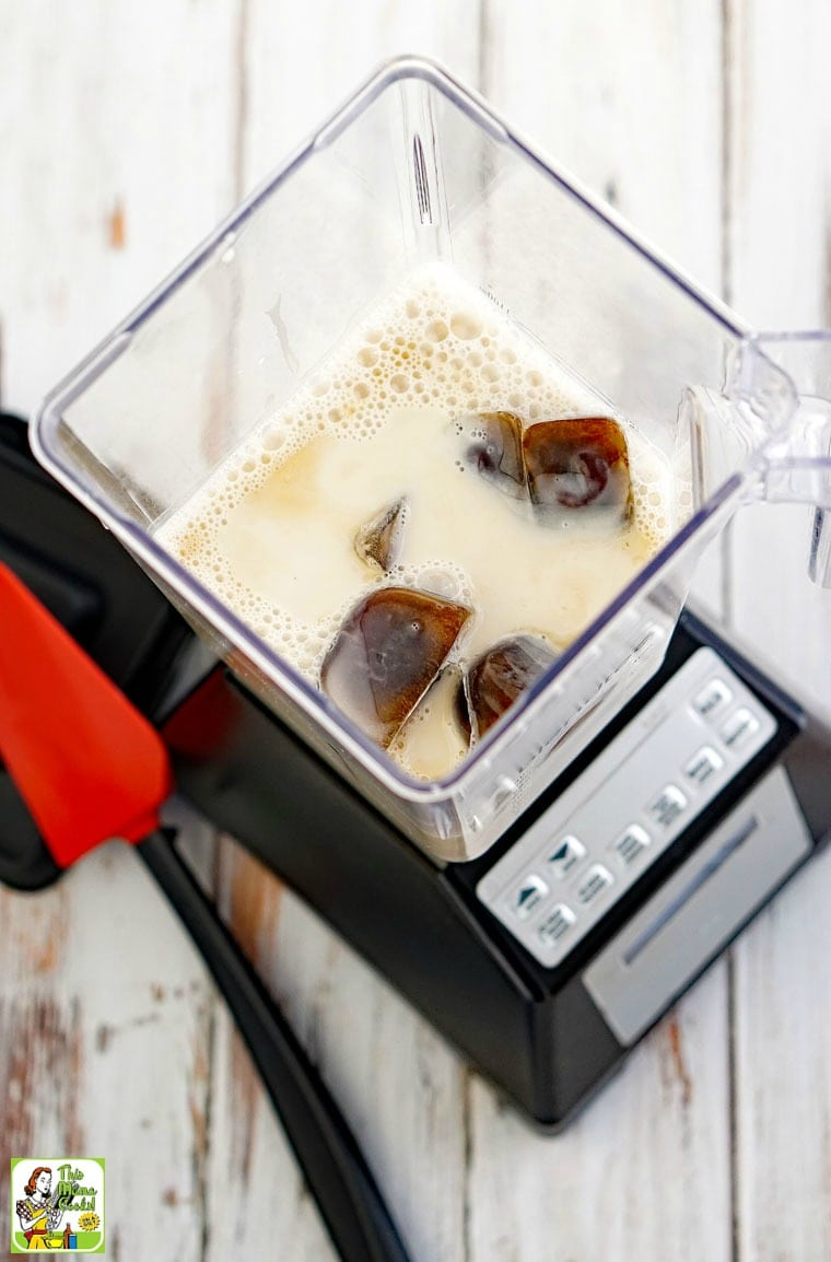 A blender filled with almond milk and cold brew ice cubes for a coffee smoothie drink.