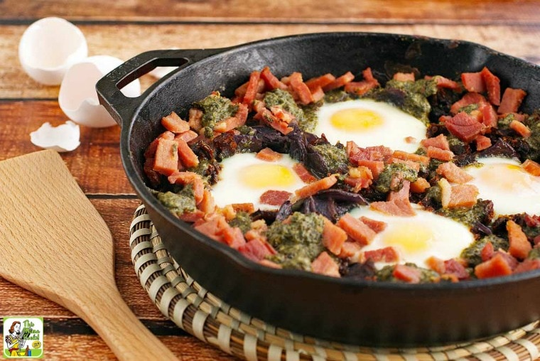 Baked eggs, ham, potatoes, sun dried tomatoes, and pesto in a skillet with a wooden serving spoon