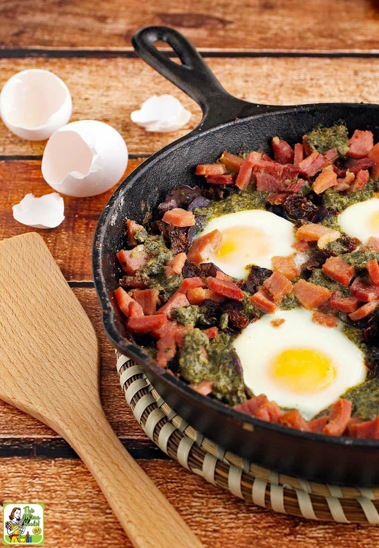 Baked eggs, ham, potatoes, and pesto in a skillet