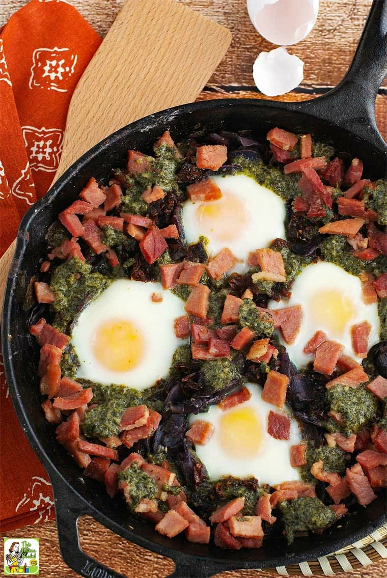 Overhead shot of baked eggs, ham, sun dried tomatoes, potatoes, and pesto in a cast iron skillet