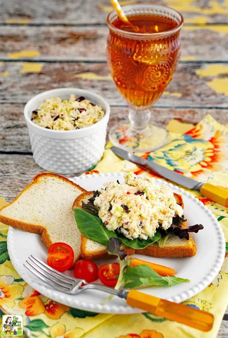 Easy Chicken Salad Sandwich on a plate with tomato, lettuce, cutlery, and a glass of iced tea
