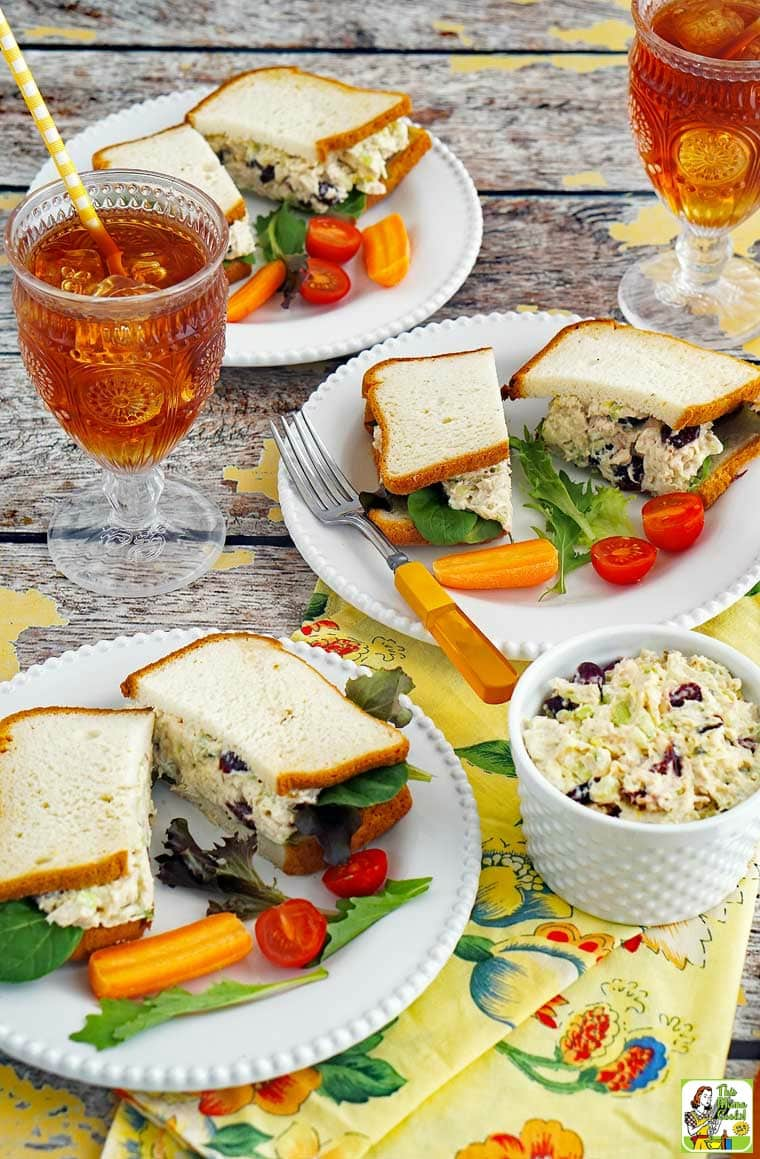 Overhead shot of a Chicken Salad Sandwiches on plates with tomato, lettuce, cutlery, and a glasses of iced tea with straws. Served with floral napkins with extra bowls of chicken salad.
