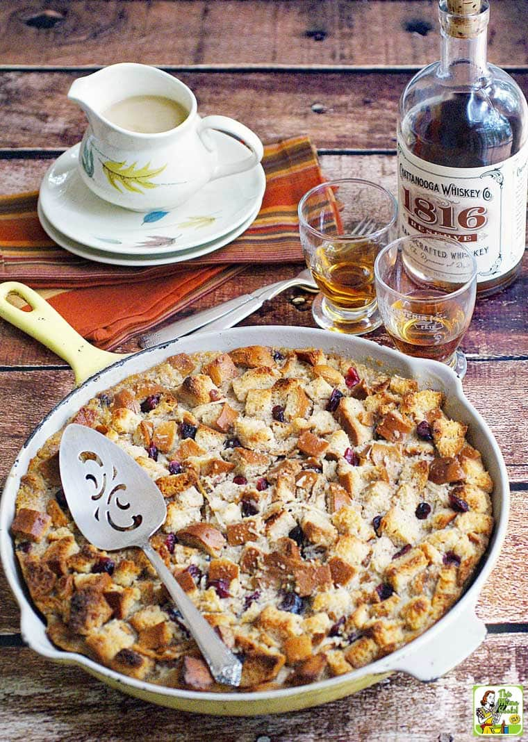 A skillet of Easy Bread Pudding Recipe with Bourbon Sauce with glasses of whiskey