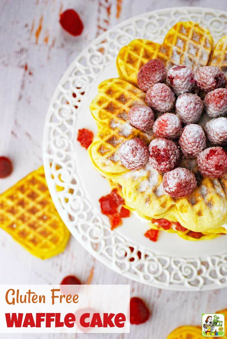 Overhead view of a waffle cake with cream cheese, jam, and sugared raspberries on a white cake stand