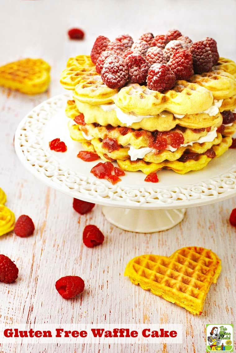 Gluten Free Waffle Cake with raspberries and powdered sugar on a white cake stand