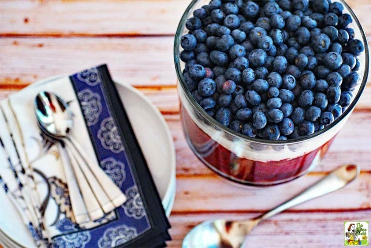 Red White and Blue Trifle with blueberries and whipped cream in a glass trifle bowl with blue napkins and serving spoons