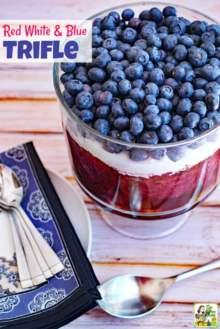 Red White and Blue Trifle with blueberries and whipped cream in a glass trifle bowl with blue napkins and spoons