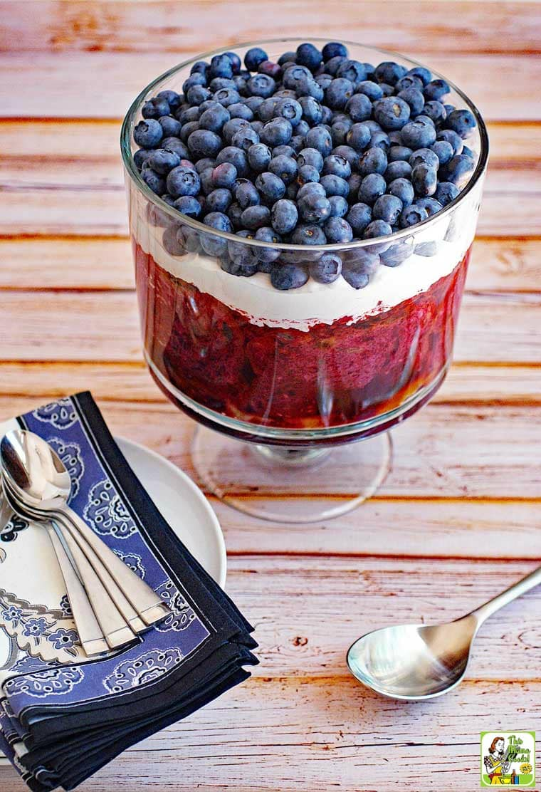 Trifle with blueberries and whipped cream in a glass trifle bowl with blue napkins and serving spoons