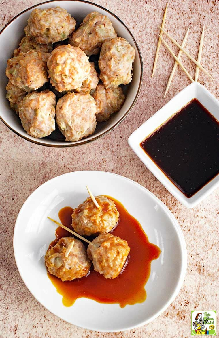 A bowl and plate of Asian style pork meatball appetizers served on toothpicks with a small bowl of dipping sauce.
