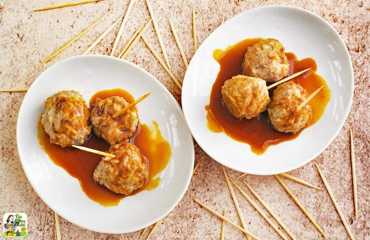 Asian Style Gluten Free Meatballs in dipping sauce served in white plates with toothpicks.