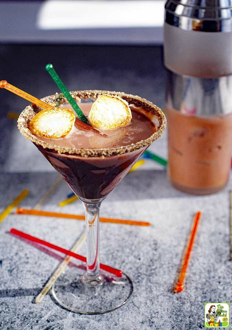 Chocolate Smores Martini served with toasted marshmallows. Cocktail shaker in background.