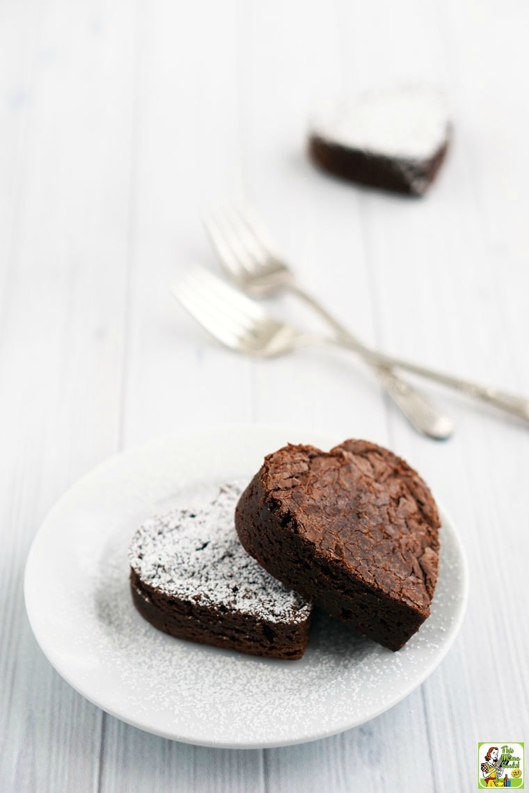 A white plate with two heart shaped brownies with forks and another brownie in the background.