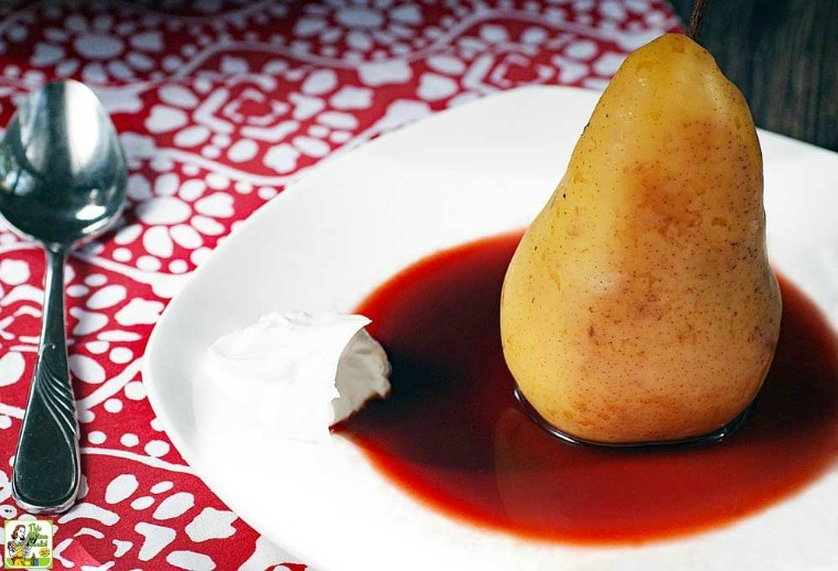 A dish with a Slow Cooker Poached Pear in cherry sauce on a red and white napkin with spoon.