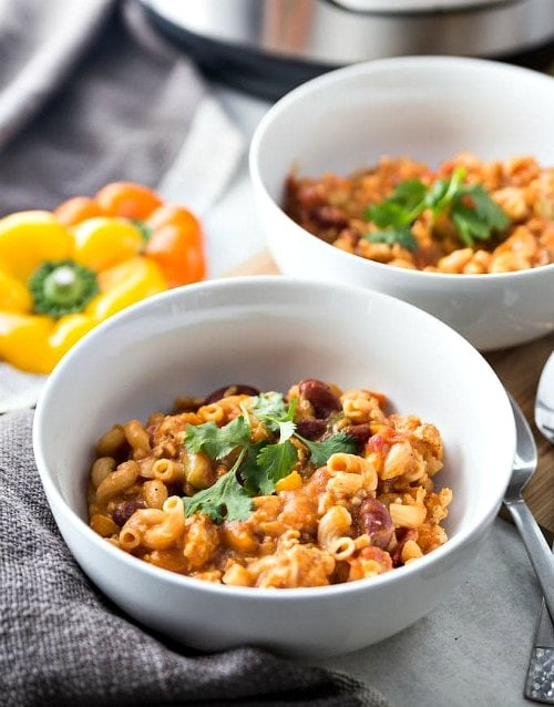 Bowl of Healthy Instant Pot Chili Mac with napkin and spoons.