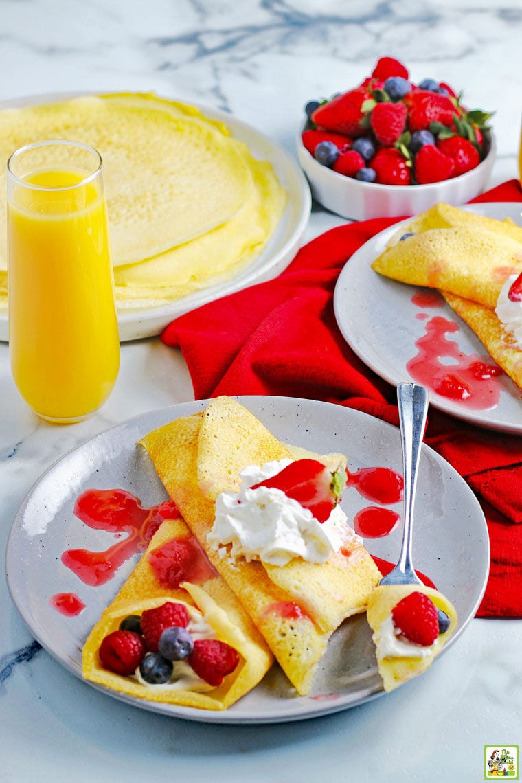 A berry and cream filled crepes on a plate with plates of gluten free crepes, a bowl of berries and a glass of orange juice on a red cloth napkin.