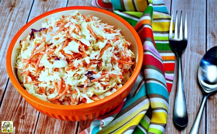 An orange bowl of Easy Coleslaw with striped kitchen towel and serving fork and spoon.