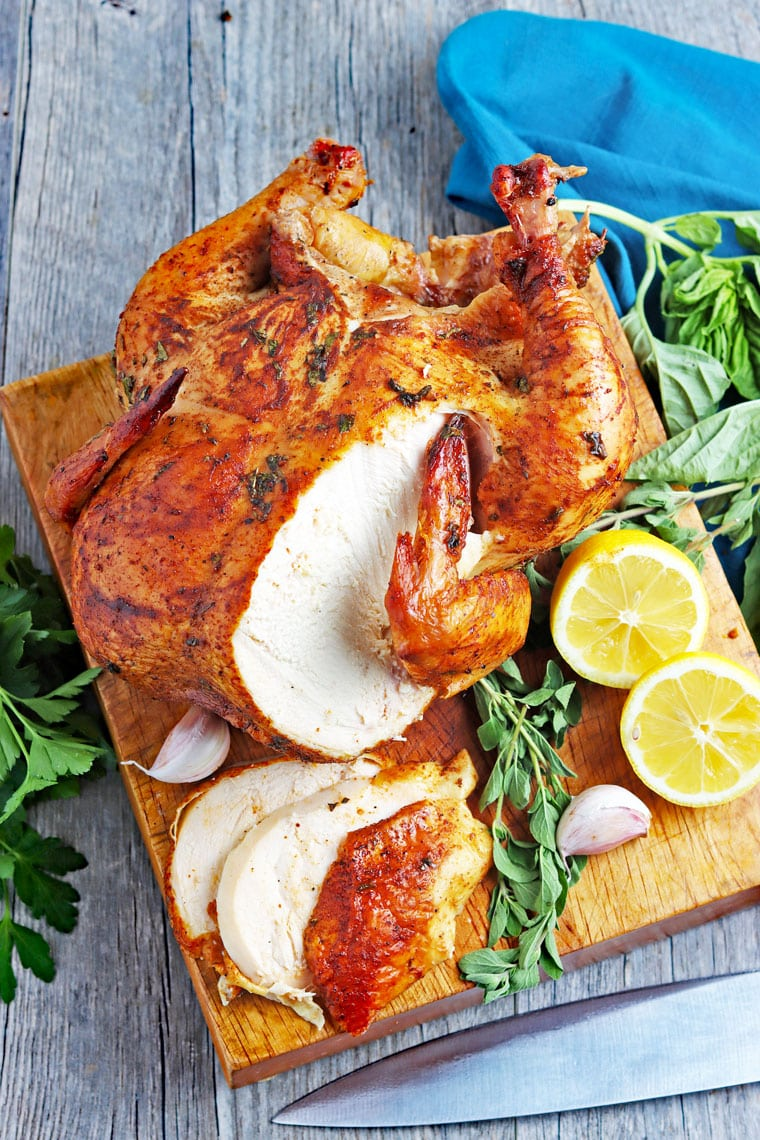 Sliced roasted chicken on a wooden cutting board with lemons, garlic and herbs with a blue cloth napkin.