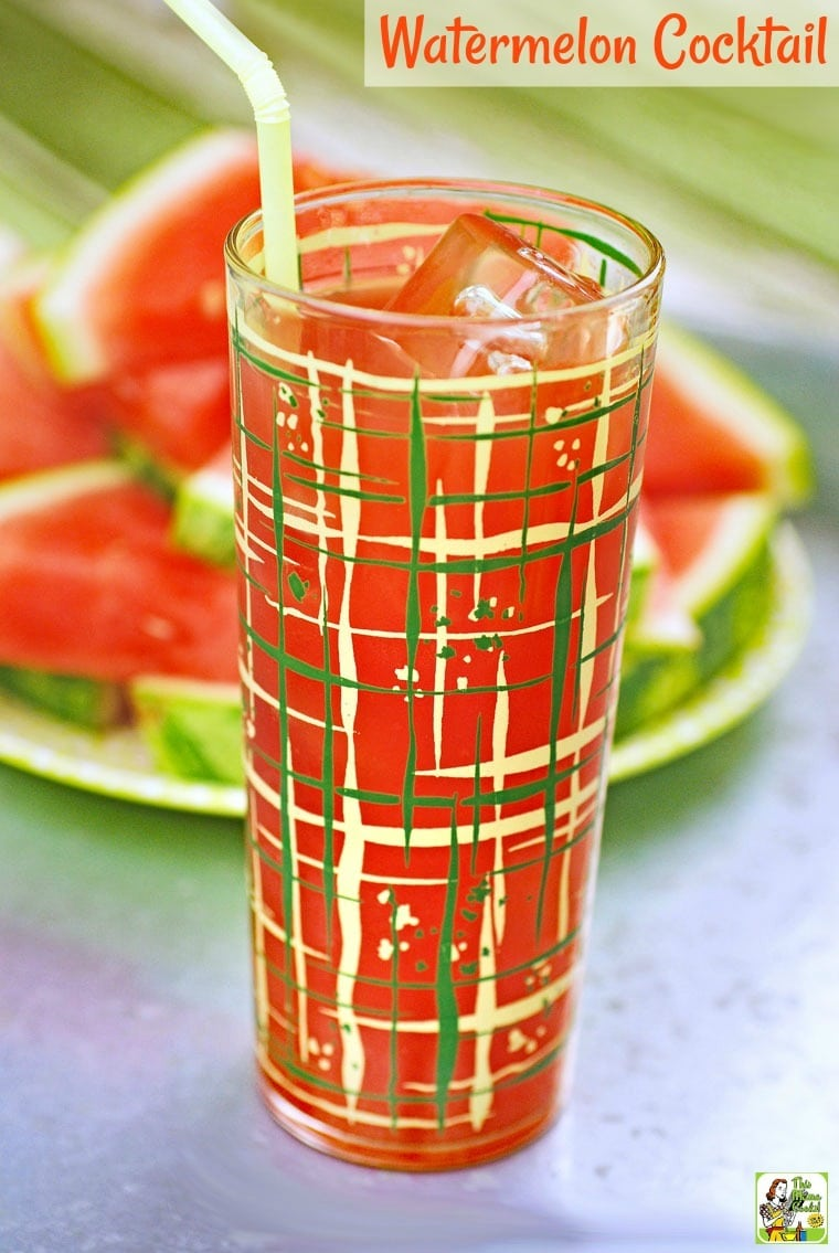 A watermelon cocktail in a tall glass on a metal tray with slices of watermelon.