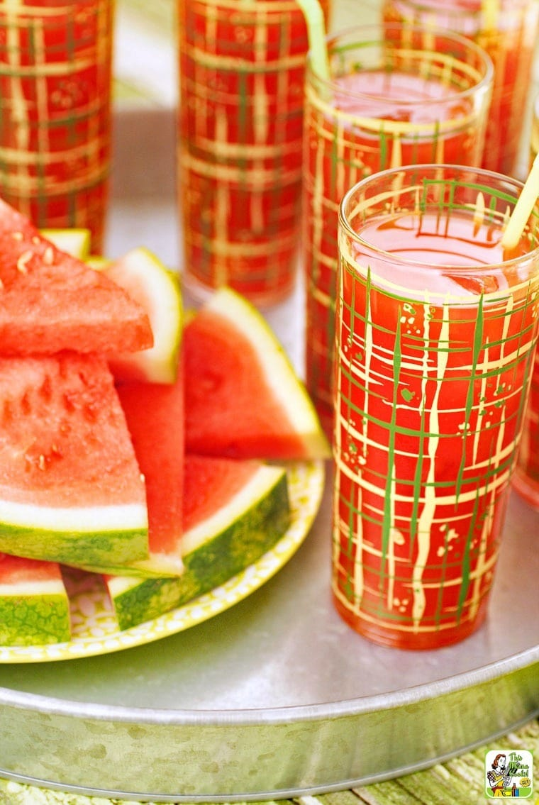 Glasses of watermelon cocktails with a plate of watermelon.