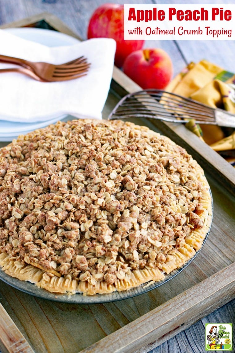 Apple Peach Pie with Oatmeal Crumb Topping on a wooden tray with plates, napkins, forks, apples, and a pie server.