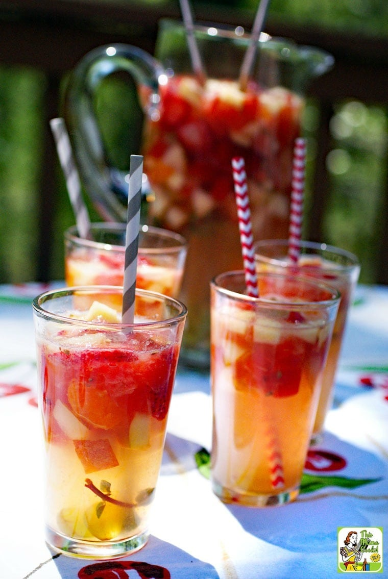Glasses of Lemonade Sangria with striped straws on a colorful tablecloth.