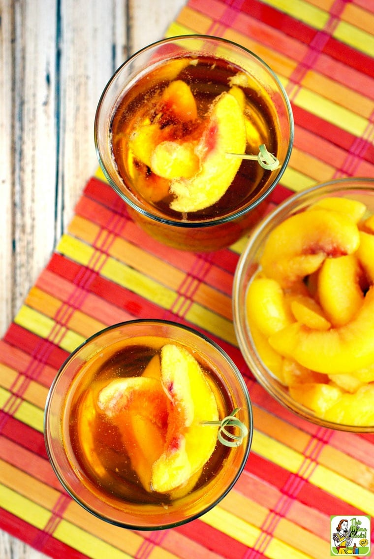 3 cocktail glasses of Peach Whiskey on a multi-colored placemat