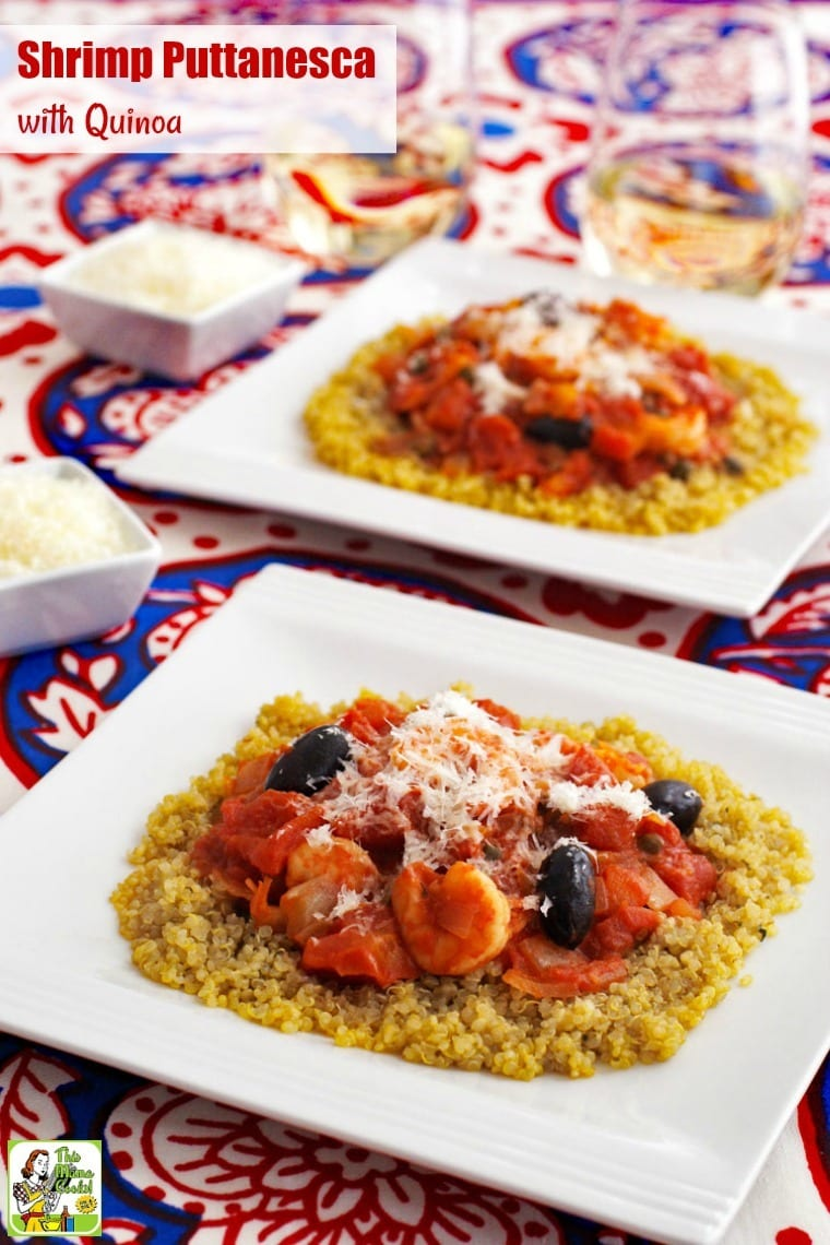 White dishes shrimp puttanesca with quinoa on a red, white and blue tablecloth, glasses of white wine, and small bowls of shredded cheese.