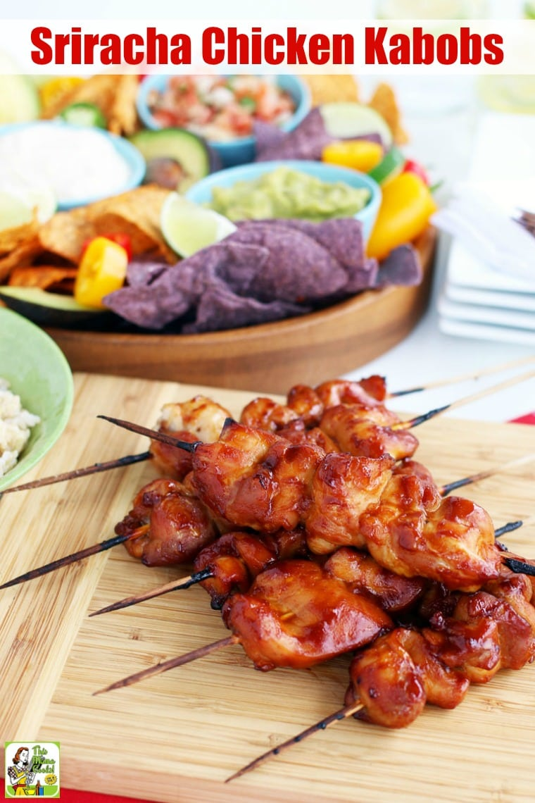 Skewers of Chicken Kabobs on a wooden platter with a wooden bowl of guacamole and tortilla chips