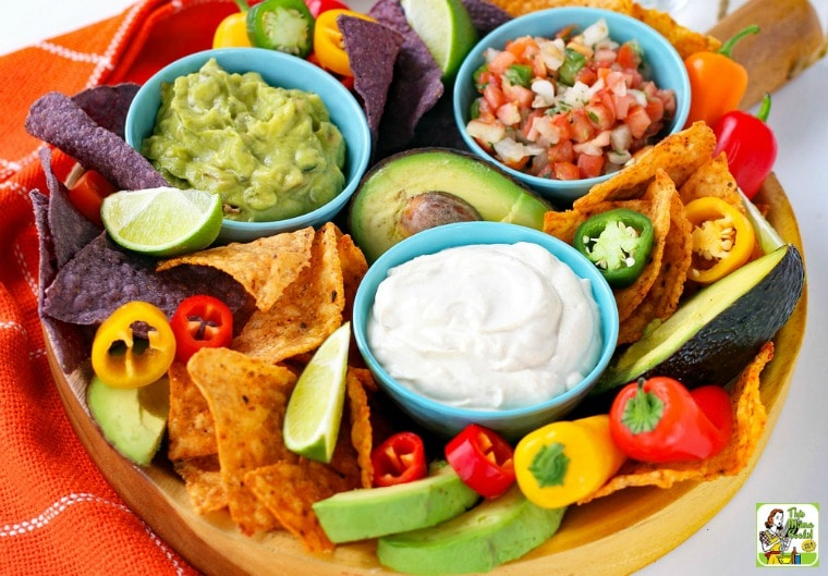 Overhead view of a platter with a bowls of Vegan Sour Cream, salsa, and guacamole with dippers of sweet peppers and tortilla chips.