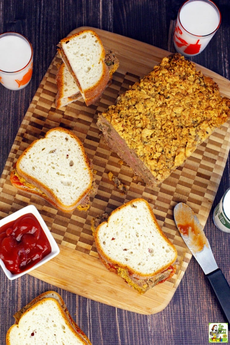 Overhead shot of Meatloaf Sandwiches, meatloaf, ketchup, and glasses of milk on a wooden cutting board