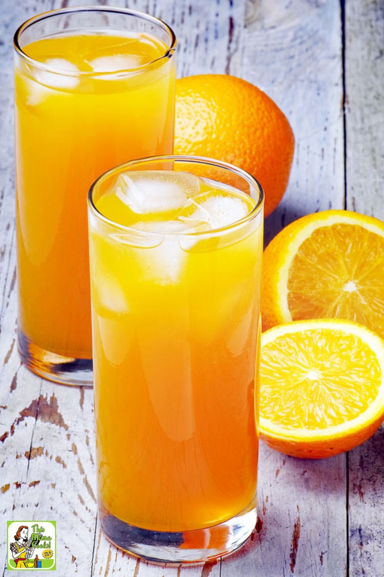 Two glasses of an orange mocktail with ice cubes and cut and whole oranges