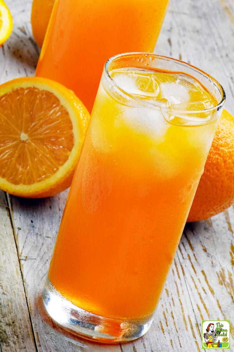 A glass of an orange drink with oranges