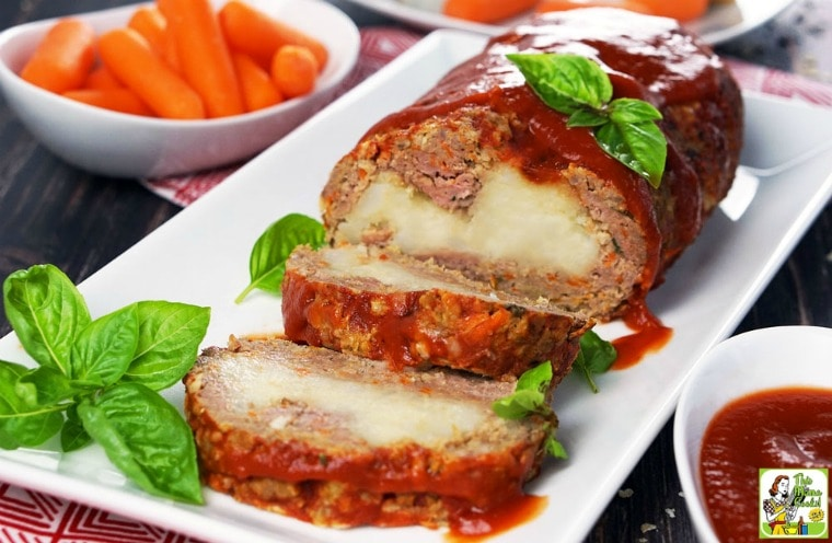 Platter of mashed potato stuffed meatloaf with condiments and carrots