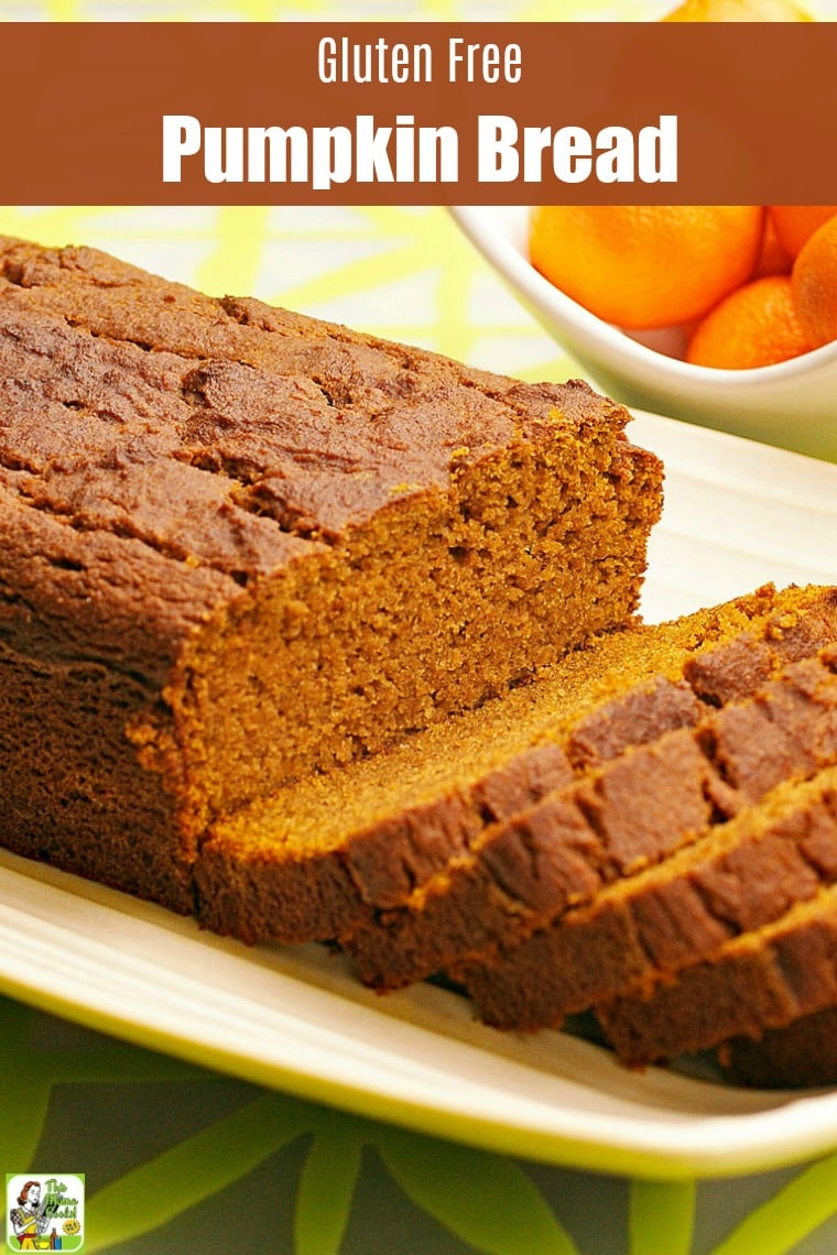 A loaf of Pumpkin Bread on a white plate with oranges in the background