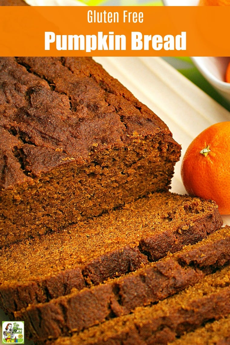 Closeup of a loaf of Pumpkin Bread sliced up on a white plate with an orange