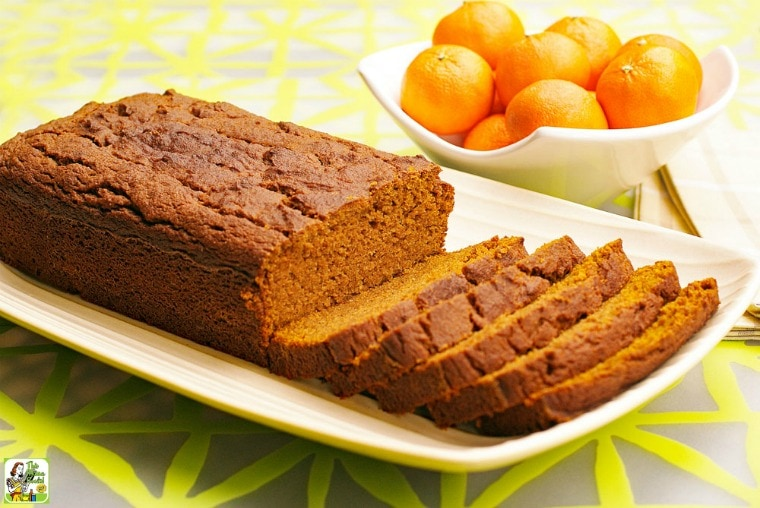 A loaf of Pumpkin Bread sliced up on a white plate with a bowl of tangarines in the background
