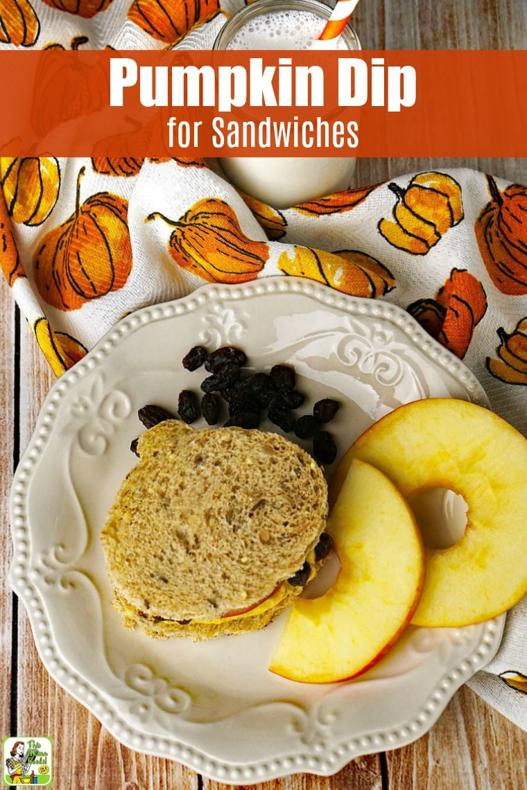Pumpkin dip sandwich on a plate with raisins and slices of apple on a pumpkin print tea towel with a glass of milk
