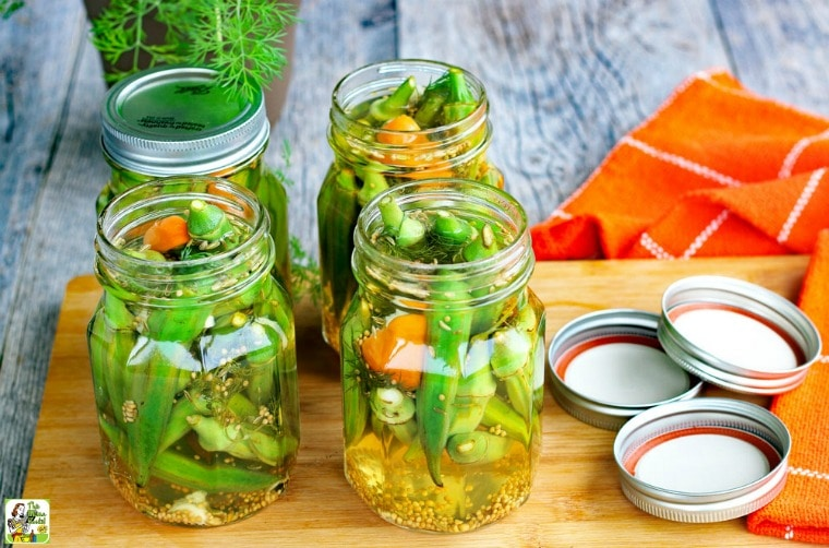 Jars of Refrigerator Pickled Okra with lids on a wooden cutting board with orange cloth napkins.