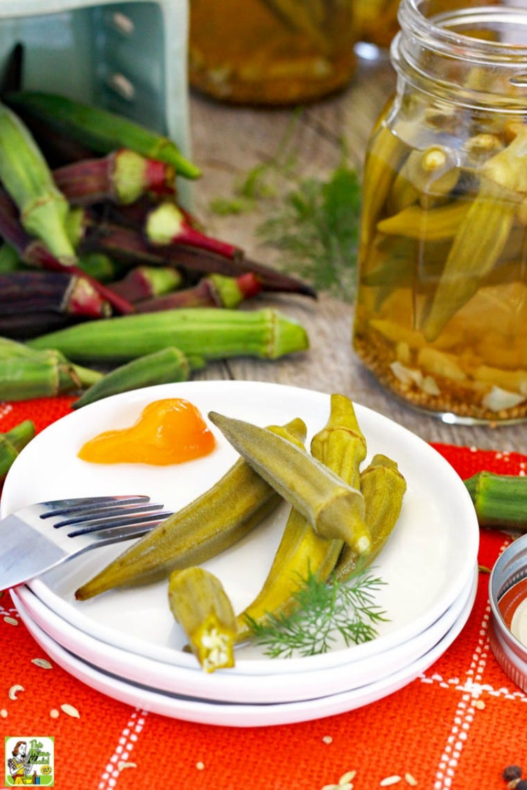 A plate of pickled okra with jars of pickled okra and raw okra in the background