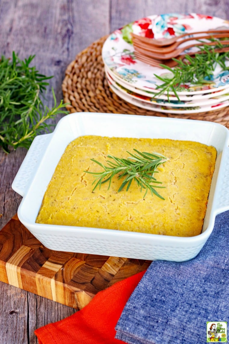 A baking dish of vegan cornbread with a sprig of rosemary and plates and forks in the background